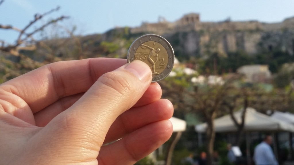 A Greek Euro coin foregrounds the Acropolis.